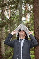 Young laughing businessman with newspaper on the head in a forest