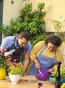 Man and woman preparing food in backyard