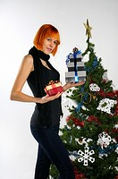 Tall woman with red hair holding Christmas presents by a decorated tree