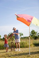 Grandfather showing granddaughter sundial in field