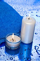 spa essentials, candles and towel on blue background