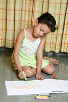 small young girl of 6 years drawing landscape in drawing book with colourful Crayons MR 487E