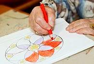 Hands of an elderly woman painting and drawing