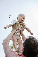 Baby girl being lifted by father