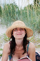 Woman wearing straw hat smiling, portrait