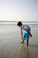 South Asian Indian boy waiting for wave on seashore trying to put small yellow paper boat in to water , Shiroda , Dist Sindhudurga , Maharashtra , Ind...