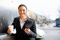 Portrait of cheerful businesswoman with takeaway coffee in one hand and mobile phone in another