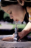 close view of gorl sipping water from a drink fountain