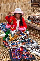 Young Peruvian Uro woman selling souvenirs, Uros islands, Lake Titicaca, Puno Region, Peru, South America