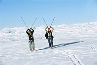 Tourists carrying ski poles