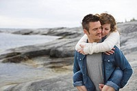 Man giving woman piggyback ride at beach