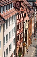 Nuremberg traditional timber framed facade with a man in Bavarian traditional clothes walking down the street