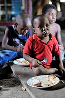 Afro-Colombian children eating a simple meal on the floor of a shabby wooden hut, Bajamar slum, Buenaventura, Valle del Cauca, Colombia, South America