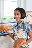 Girl holding loafs of bread and smiling