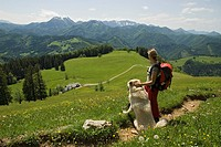 Young woman hiking with a dog, view towards Gschwendtalm in Calcareous Alps National Park, Upper Austria, Austria, Europe