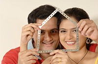 South Asian Indian man and woman looking through folding ruler as home in new flat MR705A705B