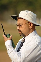 South Asian Indian cricket umpire talking to third umpire on walkie_talkie standing behind wicket on pitch MR705G