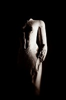 A black and white creative photograph of a ruined statue of an unknown person Karnak Temple, Egypt
