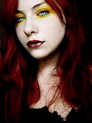 A young woman with red hair and yellow eye shadow looking at the camera