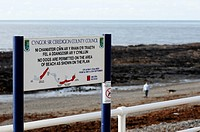 Bilingual sign, displaying restrictions on dog walking on Aberystwyth Beach, Wales