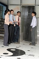 South Asian Indian businessmen and woman standing and conversation to each other at office lift MR 670E , 670F ,670G , 670H