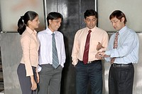 South Asian Indian businessmen and woman standing and watching time in office MR 670E , 670F ,670G , 670H