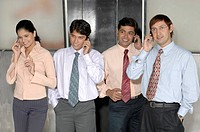 South Asian Indian businessmen and woman standing , smiling and talking on mobile wearing blue shirt , black pant , pink shirt , white shirt and tie i...