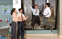 South Asian Indian businessmen and woman standing enjoying and jumping in air n office MR 670E , 670F ,670G , 670H