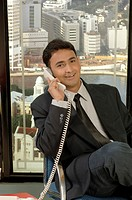 South Asian Indian businessman smiling sitting in office and talking on phone MR 670I