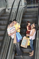 Parents carrying colourful bags with kids on escalator in shopping mall MR748E,748F, 748G,748H