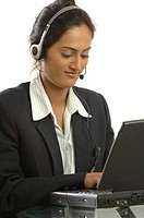 Young girl using headphones with microphone operating laptop working in call centre MR748O