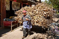 Naxi woman pulling a barrow laden with corn husks, Baisha, near Lijiang, Yunnan Province, China