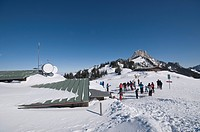 Winter sports enthusiasts at the mountain station of Mt. Kampenwand getting ready for downhill drive, looking towards Sonnenalm and the summit of Mt. ...