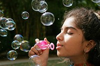 Ten years old Guajarati girl blowing out soap bubbles MR191