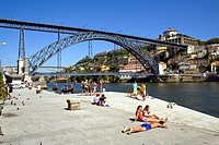 Tourists and locals sunbathing along the Douro River bank near the D  Luis I Bridge in Porto, Portugal  Unesco World Heritage site