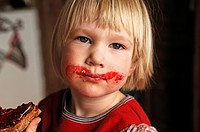 Little three-year-old boy with a jam covered mouth