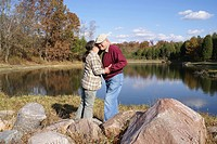 Loveing elderly couple embracing by lake