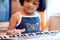 South Asian Indian five year old girl playing electronic keyboard of musical instrument called piano , Bombay now Mumbai , Maharashtra , India MR688