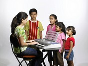South Asian Indian teacher playing keyboard and children singing in nursery school MR