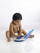 Indian baby girl wearing diaper playing with toy laptop MR702O