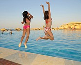 Two girls, eight years, jumping into a pool