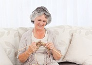 Senior knitting on her sofa at home