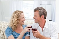 Couple drinking some red wine in the living room at home