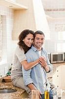 Beautiful couple hugging in the kitchen at home