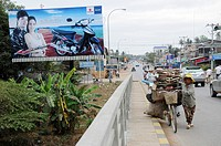 Cambodian woman pushes her bicycle past a waste-laden scooter billboard