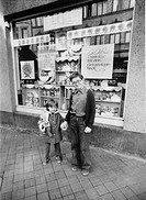 Children in front of a delicatessen with advertising for the anniversary of the Republic, East Germany, Germany, Europe, circa 1984