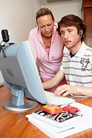 Mother and son looking at PC in room