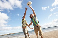 Two Teenage Boys Playing Rugby On Beach Together