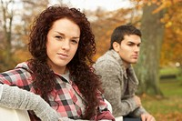 Close Up Of Teenage Couple Sitting On Bench In Autumn Park
