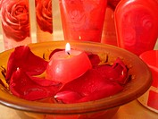 Spa essentials red rose petals on water with candle, cream and many bottles